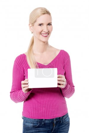 Photo for Smiling woman showing blank white ad board. - Royalty Free Image
