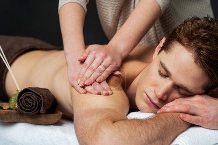 Masseur doing back massage