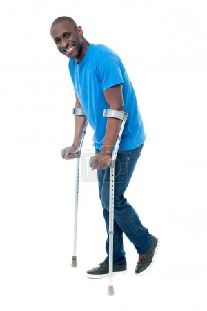 man trying to walk with crutches