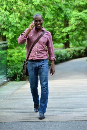 Mann läuft auf Straße und telefoniert mit Handy