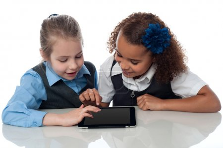 Two schoolgirls operating a digital tablet