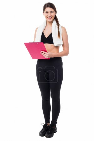 Young fit trainer holding a clipboard