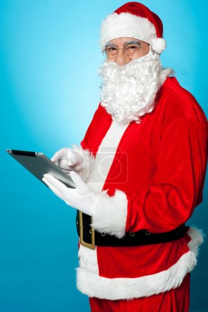 Photo for Man dressed in Santa costume using tablet pc - Royalty Free Image