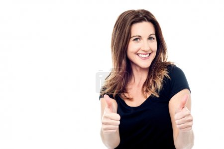 Photo for Cheerful lady showing thumbs up sign towards camera - Royalty Free Image