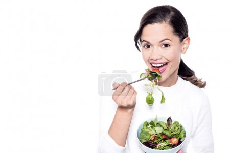 Woman eating a healthy green salad