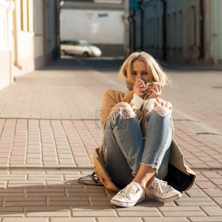 Young pretty fashionable blonde woman dressed in ripped jeans and white sweater