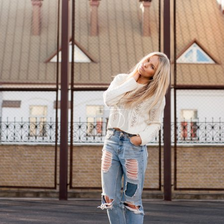 Photo for Young european girl dressed in fashionable ripped jeans and sweater posing outside on a sunny autumn day - Royalty Free Image