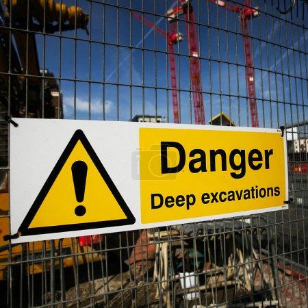 Photo pour Panneau d'avertissement sur le chantier, plusieurs grues travaillant dans le backgroun - image libre de droit