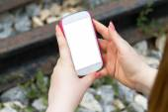 Žena držící chytrý telefon na železnici