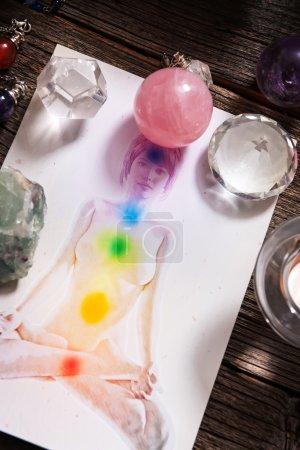 Photo pour Chakras illustrées sur le corps humain avec des cristaux naturels et pendule - image libre de droit