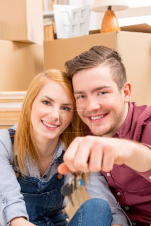 Photo for Happy couple celebrating their new home, keys in hand. - Royalty Free Image