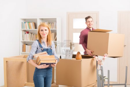 Photo for Happy young couple unpacking boxes in their new home - Royalty Free Image