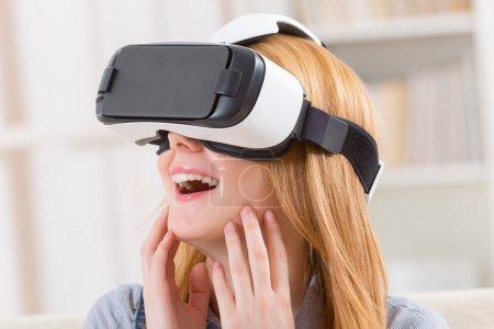 Photo pour Femme heureuse utilisant casque de réalité virtuelle à la maison - image libre de droit
