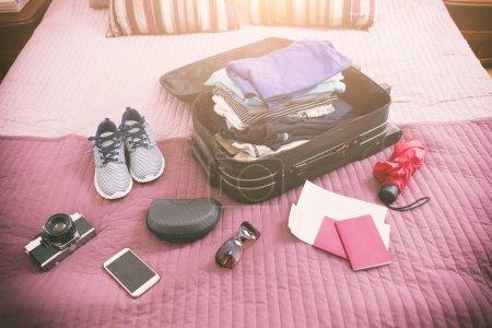 Photo pour Bagages avec pile de vêtements, appareil photo, lunettes de soleil et autres articles sur le lit - image libre de droit