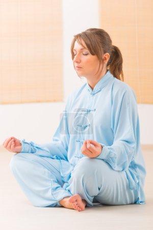Photo pour Belle femme méditant en portant des vêtements professoraux, chinois orythe à la salle de gym - image libre de droit