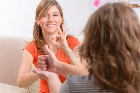 Photo pour Femme sourde et souriante apprenant le langage des signes et parlant avec son professeur - image libre de droit