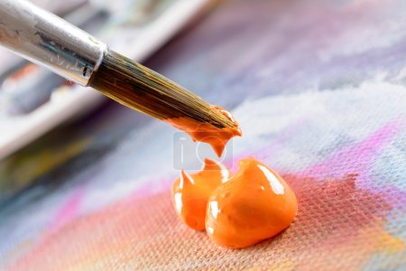 Photo for Professional acrylics orange paint on canvas and loaded brush - Royalty Free Image