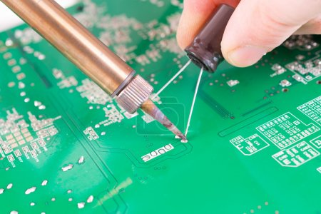 Photo for Serviceman soldering capacitor on PCB with soldering iron in the service workshop - Royalty Free Image