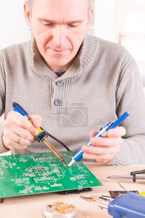 Serviceman soldering on PCB