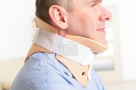 Man with a surgical cervical collar suffering from...