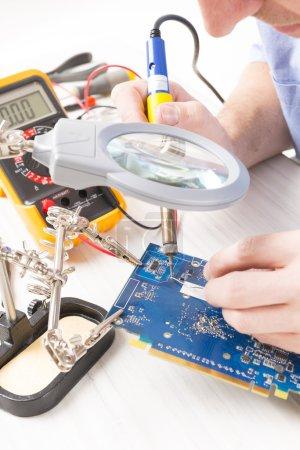 Photo pour Serviceman soldering PCB with soldering iron in the service workshop - image libre de droit