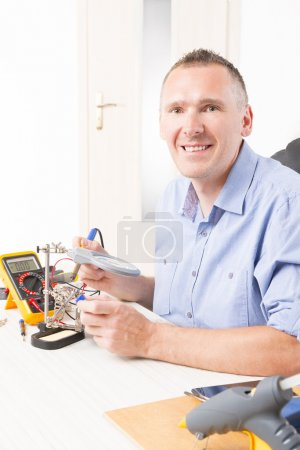 Photo for Soldering connector with third hand at the electronic workshop - Royalty Free Image