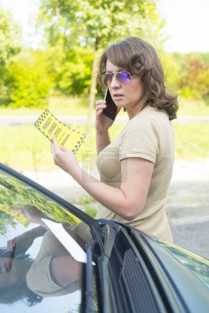 woman looking on parking ticket