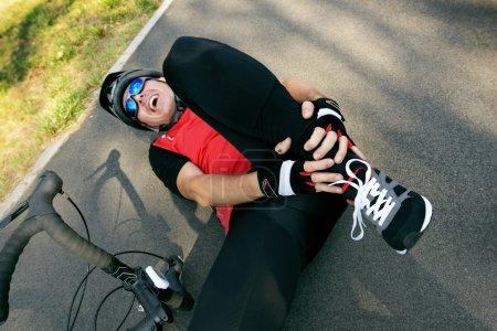 Photo pour Accident de vélo. motard tenant sa cheville . - image libre de droit