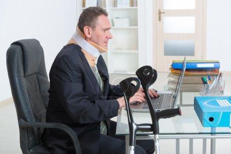 Foto de Empresario en el trabajo usar cuello ortopédico con muletas - Imagen libre de derechos