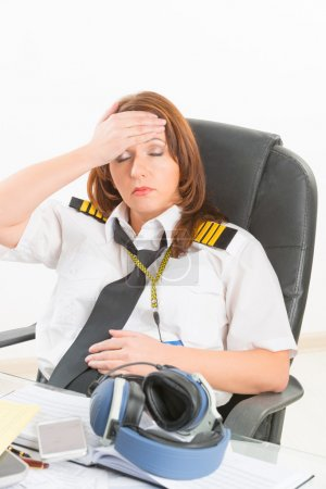 Tired woman airline pilot in the office