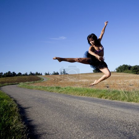 Athletic and spectacular jump of a dancer over a road.