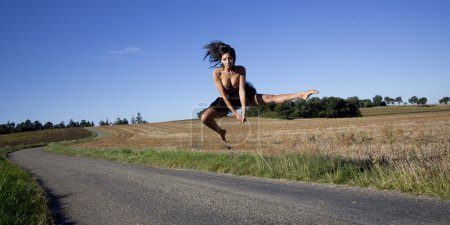 Spectacular jump of a dancer over a country road.