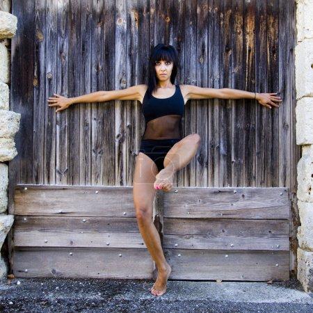 Dancer with a black leotard against a wooden door.