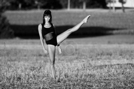 Barefoot sportswoman balances perfectly in a field stubble.