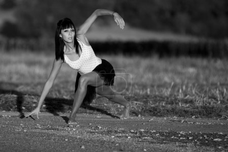 Barefoot woman in gymnastics on a country road.