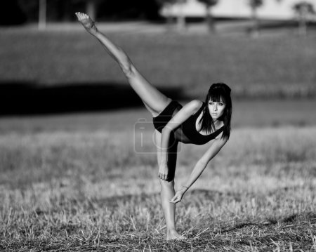 Barefoot dancer balances on one leg in a field.