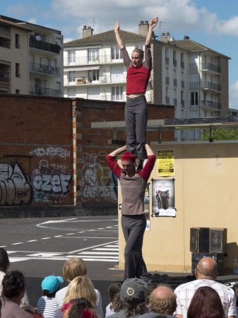 Female acrobat standing on the shoulders of his partner in the street .