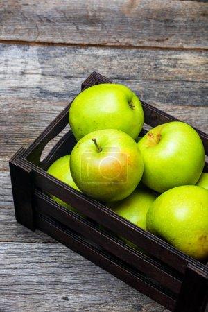 Photo pour Caisse en bois avec pommes vertes mûres sur table en bois. - image libre de droit