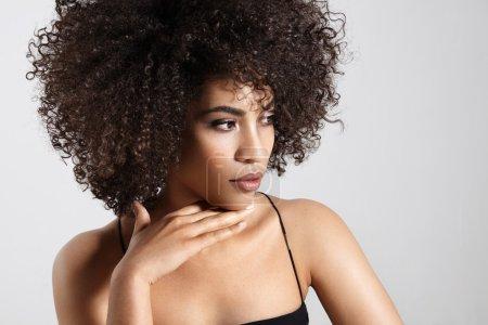 Foto de Bonita mujer negra con pelo afro rizado en estudio, de la mano en el mentón - Imagen libre de derechos