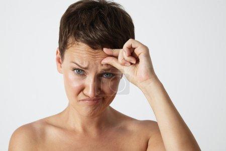 Photo pour Femme avec le visage en colère de découvrir des rides sur le front, fond blanc - image libre de droit