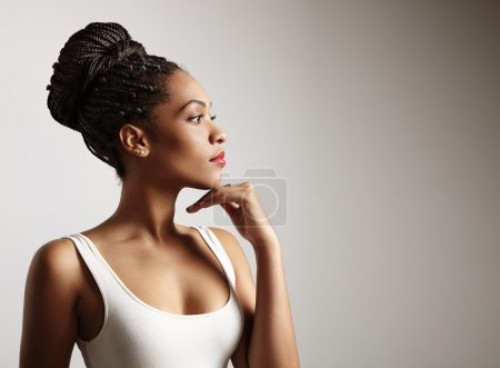 Photo for Perfect fit thoughtful black woman in white dress, hand on chin - Royalty Free Image