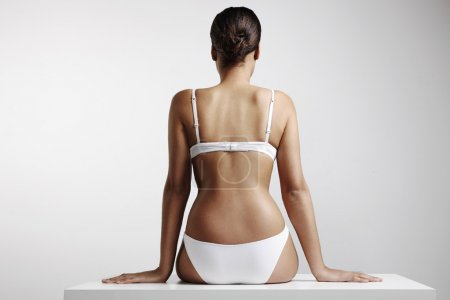 Photo for Back view of woman with perfect body sitting on table - Royalty Free Image