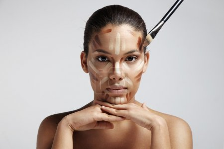 Photo pour Woman with different shades of foundation on face, hands on chin - image libre de droit