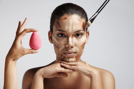 Photo pour Woman with different shades of foundation on face and hand holding pink sponge, hands on chin - image libre de droit