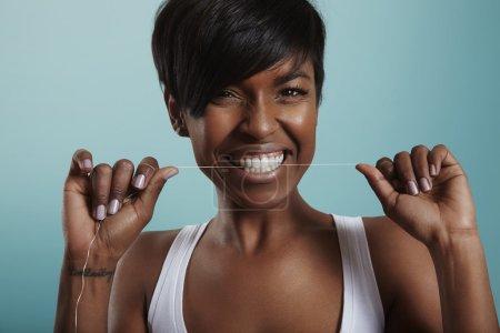 Photo pour Jeune femme nettoyer les dents blanches avec de la soie dentaire - image libre de droit
