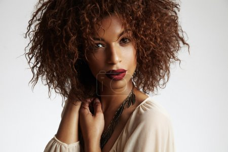 Photo for Beautiful thoughtful black woman with curly hair and red lips, hands on neck - Royalty Free Image