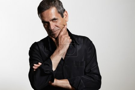 Photo for Serious senior man wearing black shirt with hand on chin and crossed arms - Royalty Free Image