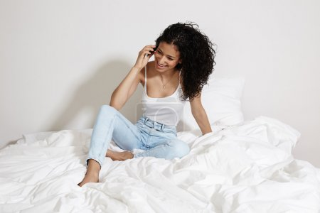 Photo for Happy young girl talking on  phone sitting on a bed - Royalty Free Image