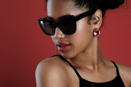 woman in earrings and sunglasses posing