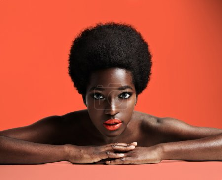 Photo for Beautiful black woman with afro hair in studio on orange background - Royalty Free Image